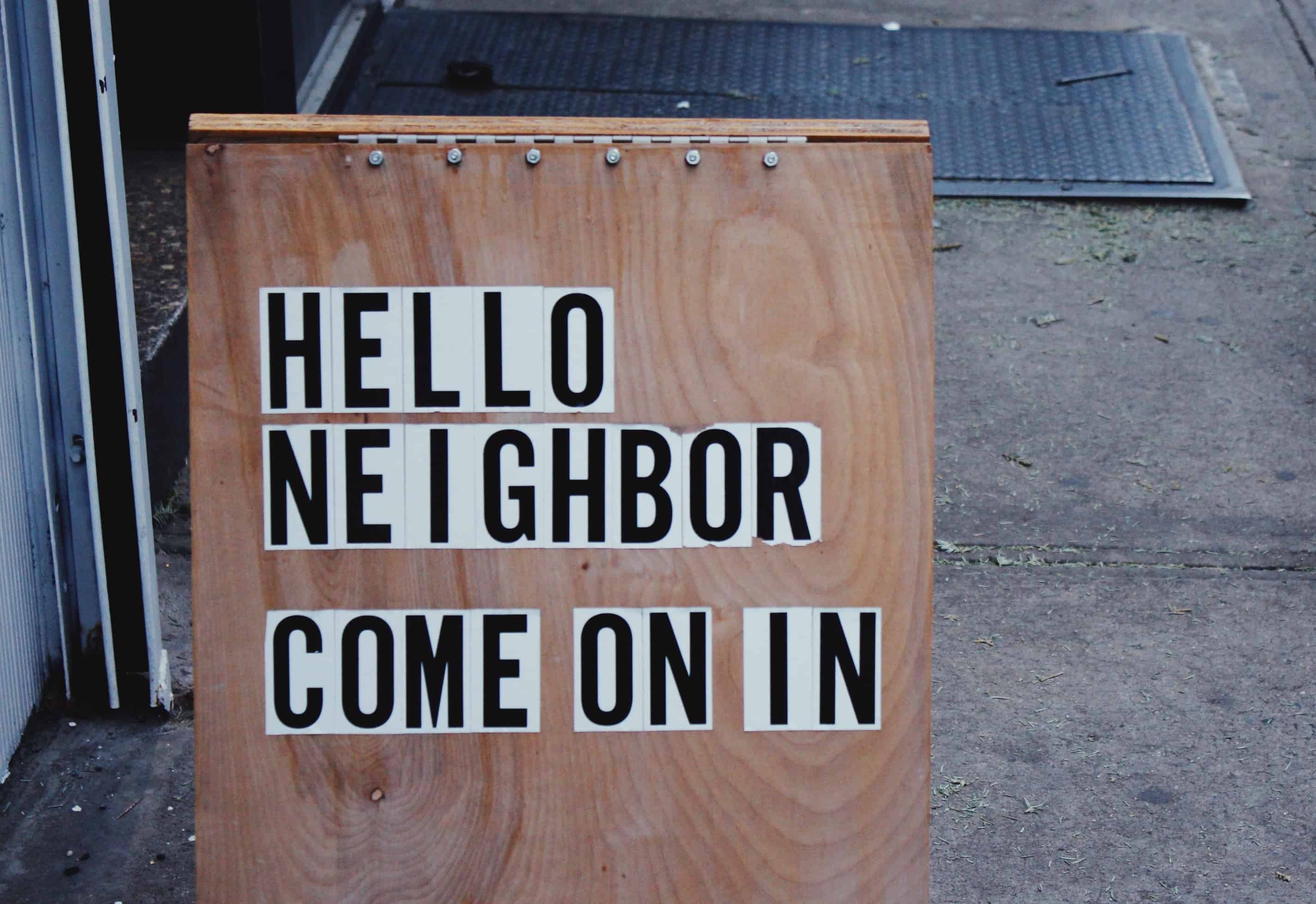An a-frame sign that reads: Hello Neighbor, come on in.